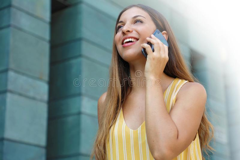 Happy successful business woman walking in the street and talking with mobile phone royalty free stock photography