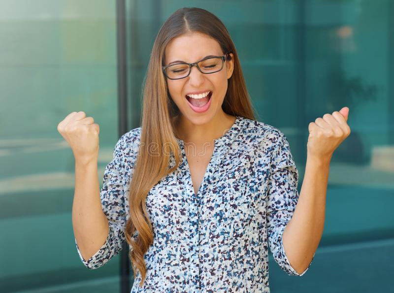 Happy successful business woman winning with arms up screaming of joy with closed eyes outdoor.  royalty free stock images