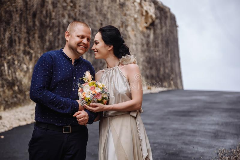 Happy successful couple travalers at Bali, Indonesia. Near big rocks royalty free stock images