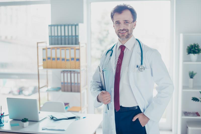 Happy successful doctor in glasses standing at the office, holding clip board. His workplace is bright and modern royalty free stock images