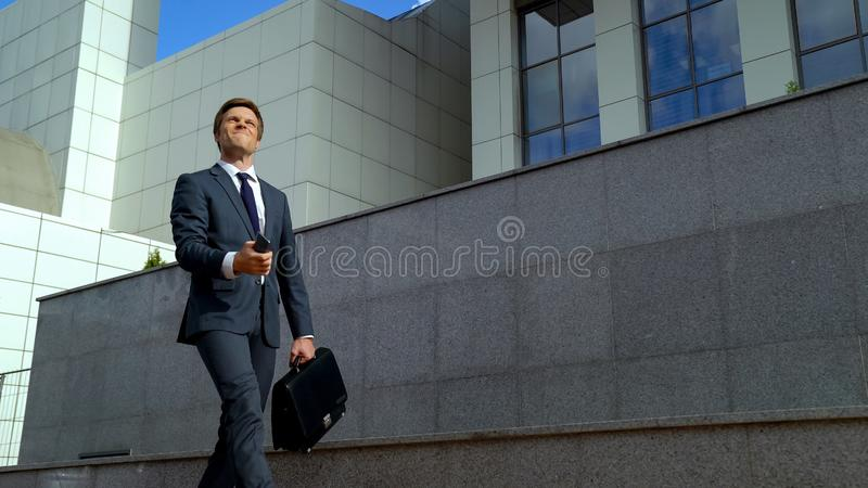 Happy successful employee holding phone celebrating career success, breakthrough stock photo