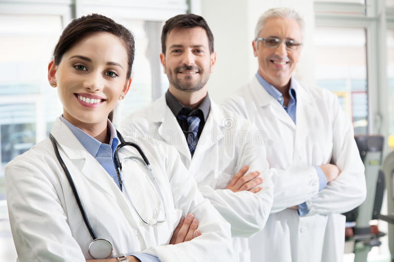 Happy successful medical team in a hospital. Standing in their white lab coats with folded arms in a receding staggered row with focus to an attractive female stock photography