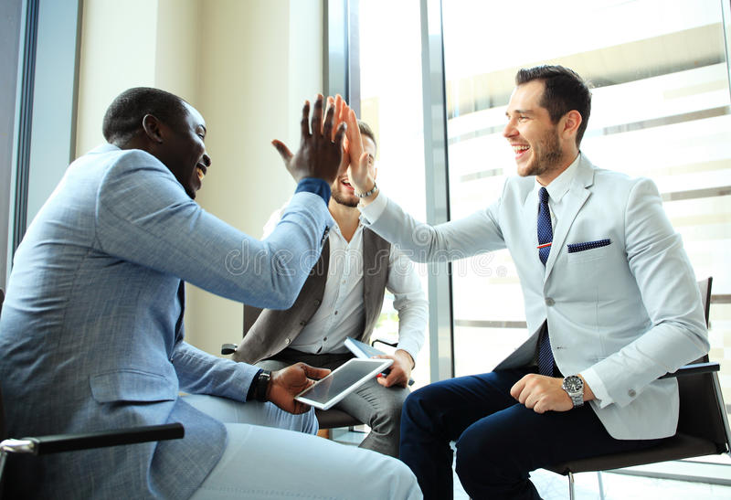 Happy successful multiracial business team giving a high fives gesture as they laugh and cheer their success. stock photography