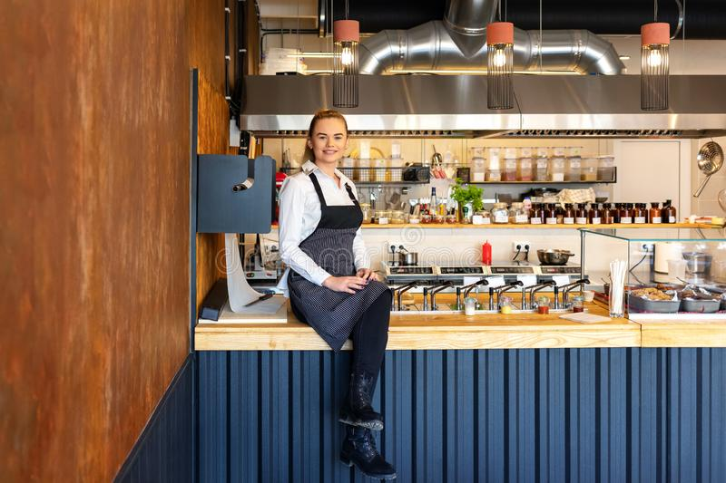 Happy successful new restaurant owner sitting on counter proud of her small business. Happy successful restaurant owner sitting on counter proud of her small royalty free stock photo