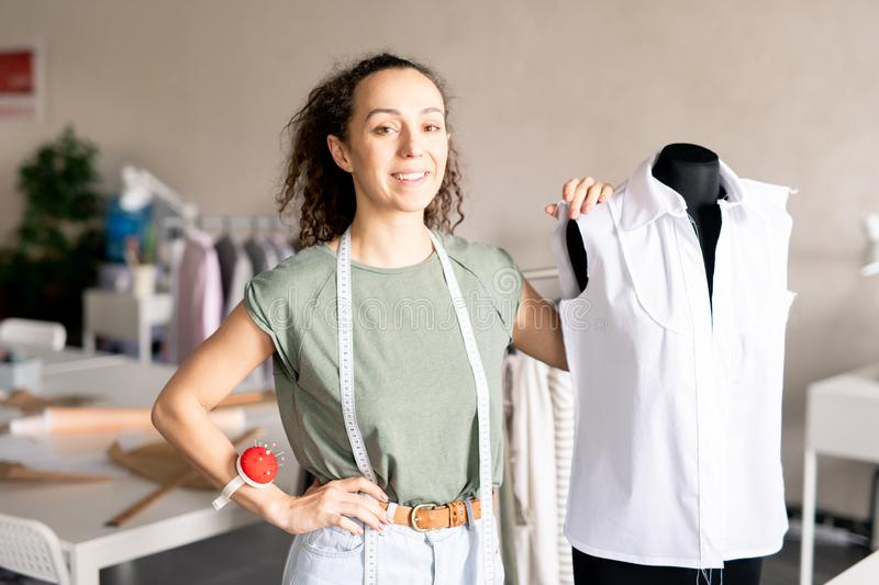 Tailor by dummy. Happy successful self-employed seamstress standing by dummy with unfinished white blouse on in her workshop royalty free stock image