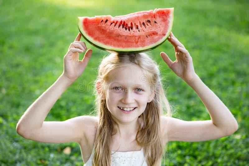 Girl eating watermelon. Happy summer - beautiful blond little girl eating watermelon on a green lawn stock photo