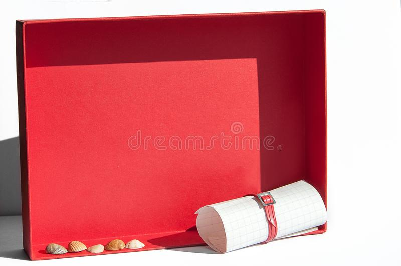 Happy summer concept, memories from travel and love notes. Twisted scroll of paper and seashells on a red box background. royalty free stock photo