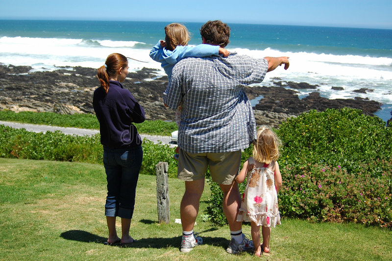 Happy summer family. A happy caucasian family on vacation by the sea. The father is pointing with his white arm to the ocean showing the waves to the kids