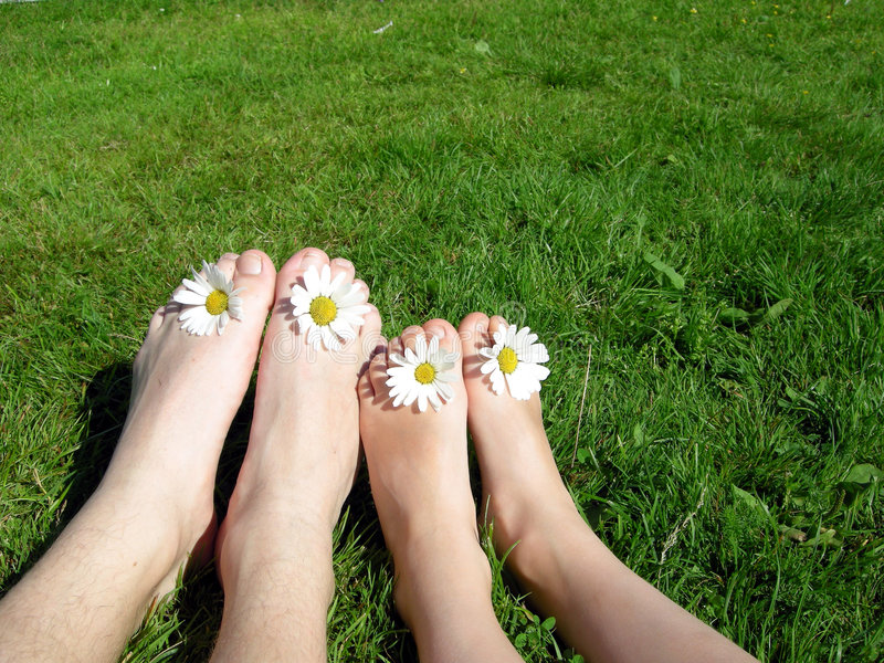Happy summer feet. Two children sitting on the grass with flowers between the toes royalty free stock photo