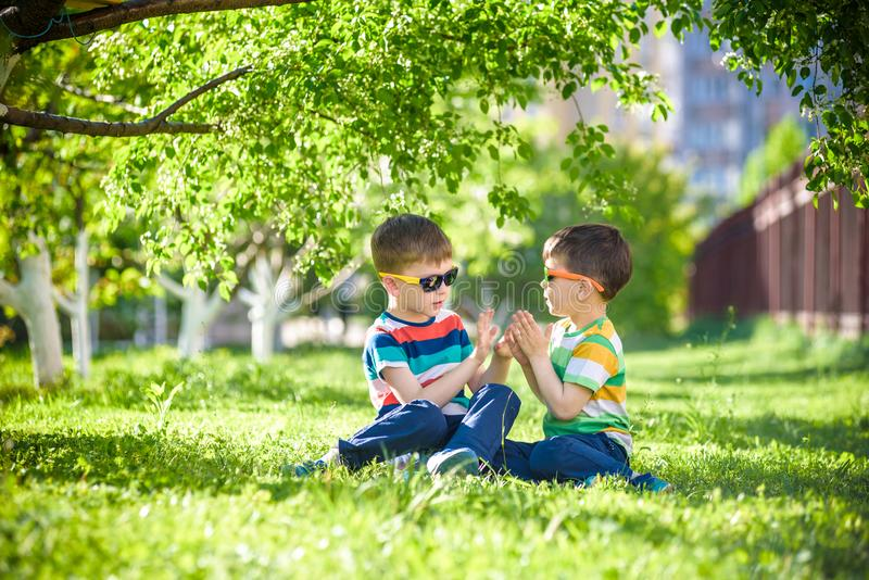 Happy summer holidays. Two happy children on a green lawn at a s royalty free stock photo