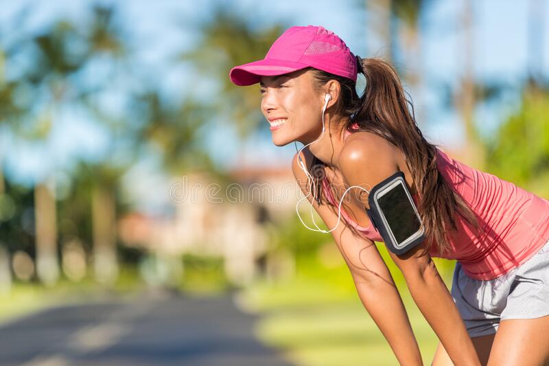 Happy summer running woman runner listening to music on phone sports armband with touchscreen and headphones earphones. On city street, active lifestyle royalty free stock photo