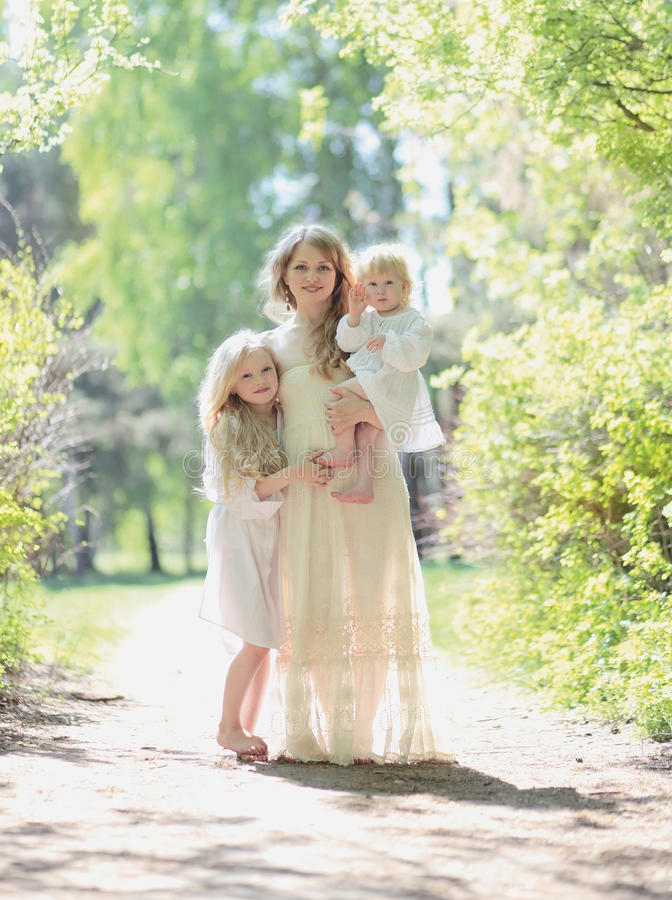 Happy sunny family, mother with her daughters royalty free stock photography