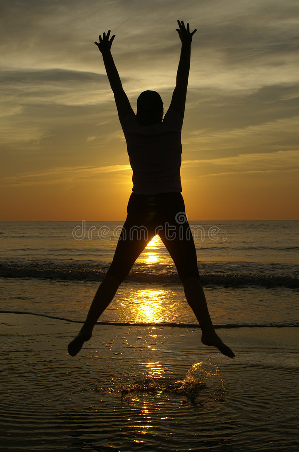 Happy sunset. A happy person jumps up on the beach with the sunset in the background stock photo