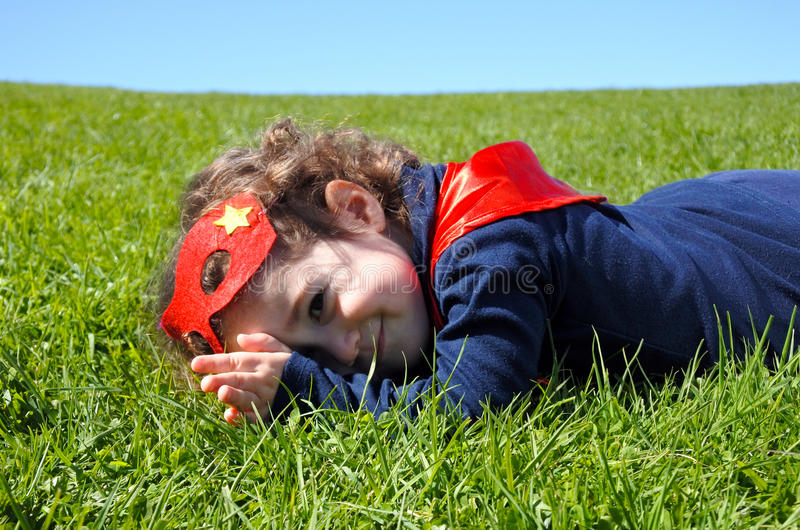 Happy Superhero toddler lay on green grass. Concept photo of Super hero, girl power, play pretend, childhood, imagination. Real people royalty free stock photo