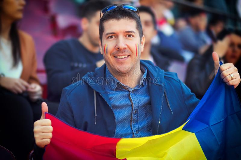 Happy supporter holding Romanian national flag in hands at international sport event – man in the stands of stadium cheering. Happy supporter holding royalty free stock photography