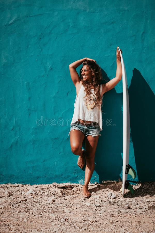 Happy surfer girl with surfboard in front of blue wall. Surfer girl with surfboard in front of blue wall royalty free stock images
