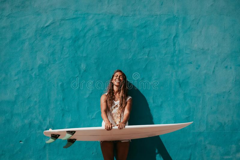 Happy surfer girl with surfboard in front of blue wall. Surfer girl with surfboard in front of blue wall stock photo