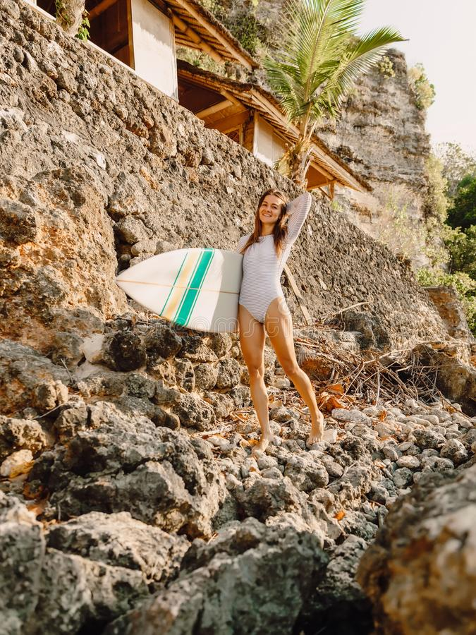 Happy surfer woman with surfboard on a rocky shore. Happy surfer woman with surfboard on a shore royalty free stock photo