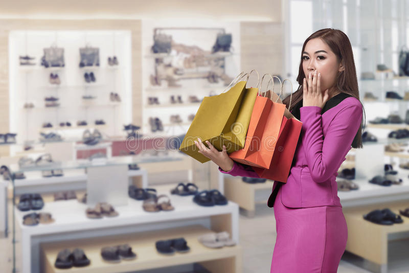 Happy surprised asian business woman with shopping bag in her ha royalty free stock photo