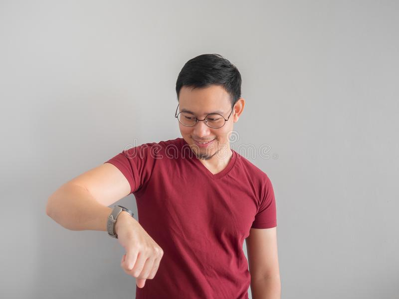 Happy and surprised man who is looking at his watch. Happy and surprised Asian man who is looking at his watch stock image