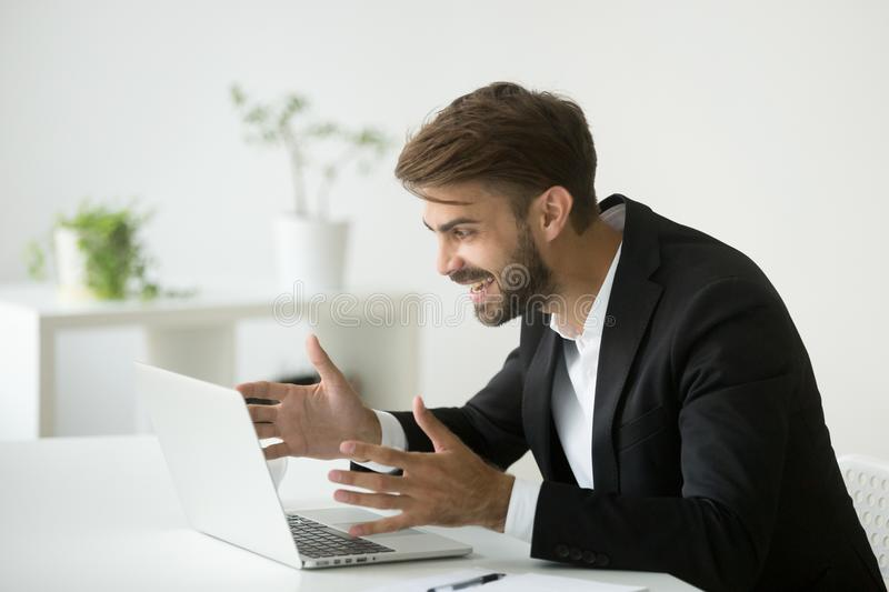 Happy surprised businessman looking at laptop excited by online. Happy surprised businessman in suit looking at laptop screen excited by online project result stock photos