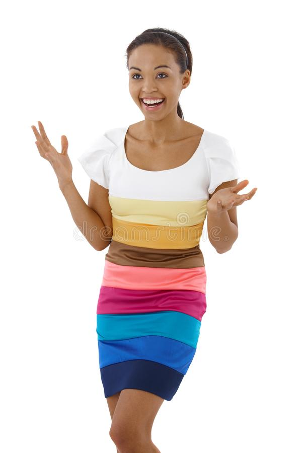 Happy surprised girl in multicolour dress. Happy surprised girl standing in multicolour dress, raising arms, laughing stock photography