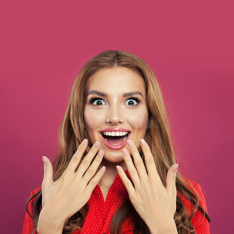 Happy surprised girl portrait. Beautiful young excited woman on colorful bright pink background stock photos