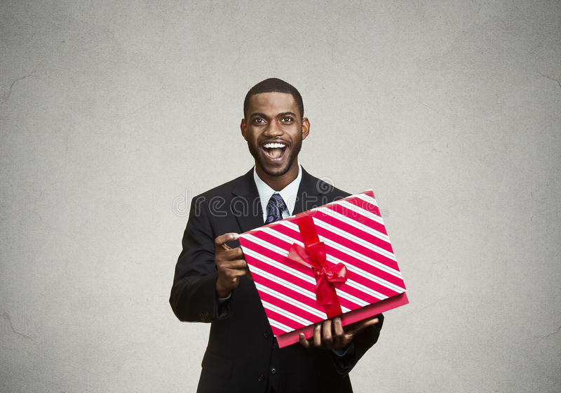 Happy, surprised man receiving gift from someone. Closeup portrait young happy excited man opening red gift box, pleased, grateful with what he received royalty free stock images