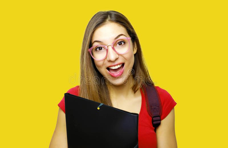Happy surprised student with glasses looking at the camera on yellow background stock photo