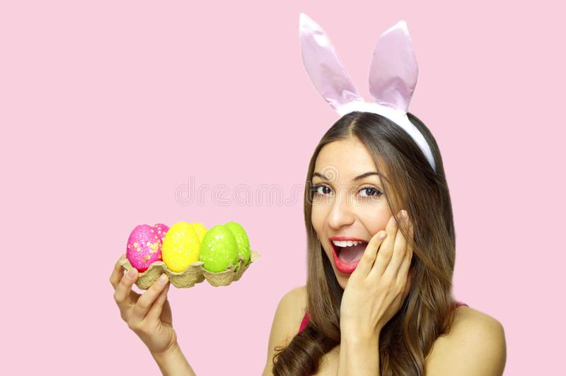 Happy surprised woman with bunny ears holdings egg carton of colorful Easter eggs looking at camera over pink background. Copy spa stock photo
