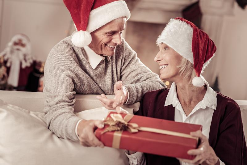 Happy surprised woman looking at husband and holding a present. Unexpected surprise. Happy surprised pretty women in a red hat sitting on the sofa in the bright royalty free stock photography