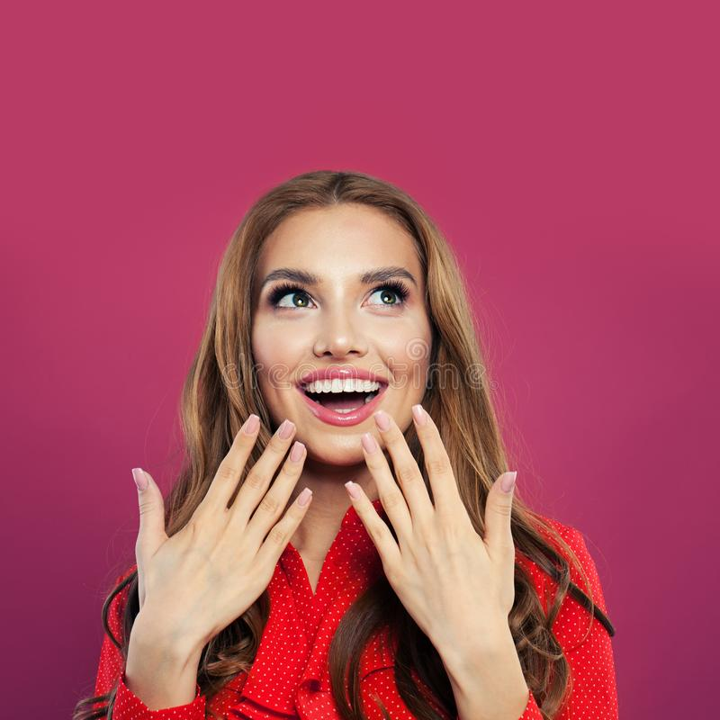 Happy surprised woman looking up and laughing portrait. Pretty excited girl on colorful bright pink background royalty free stock image
