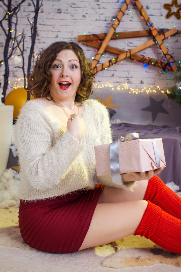 Happy surprised woman opening gift box near decorated christmas stock images