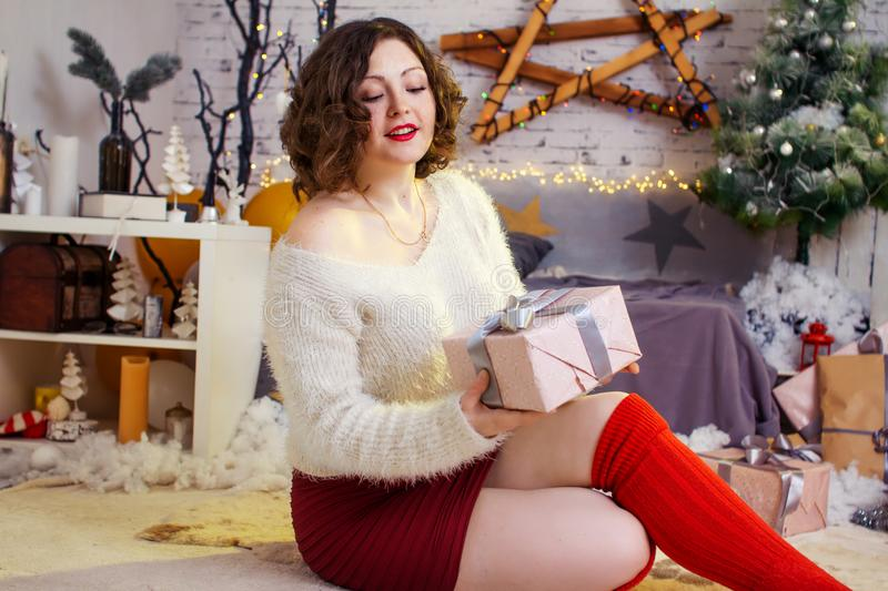 Happy surprised woman opening gift box near decorated christmas royalty free stock photography