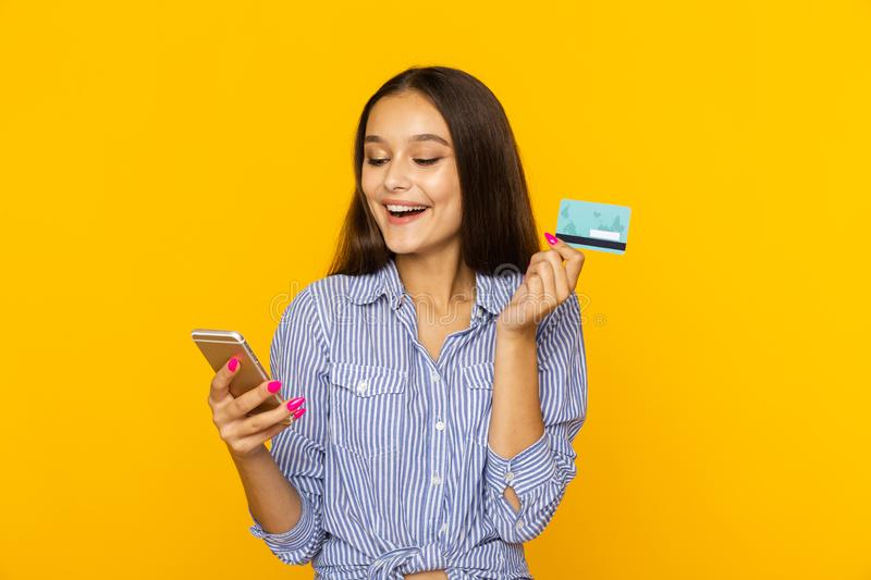 Happy surprised woman with phone and credit card. Shopping online concept. Happy surprised woman with phone and credit card. Shopping online concept stock photos