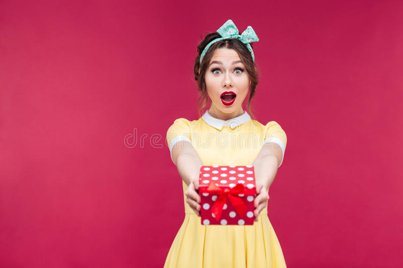 Happy surprised young woman giving you a gift box. Over pink background royalty free stock photos