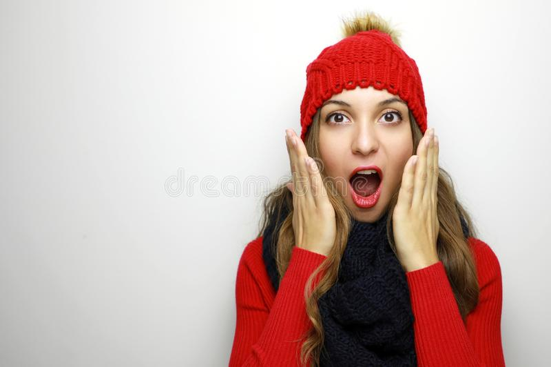 Happy surprised young woman in winter clothes on white background with copy space. Sales and discount concept. stock image