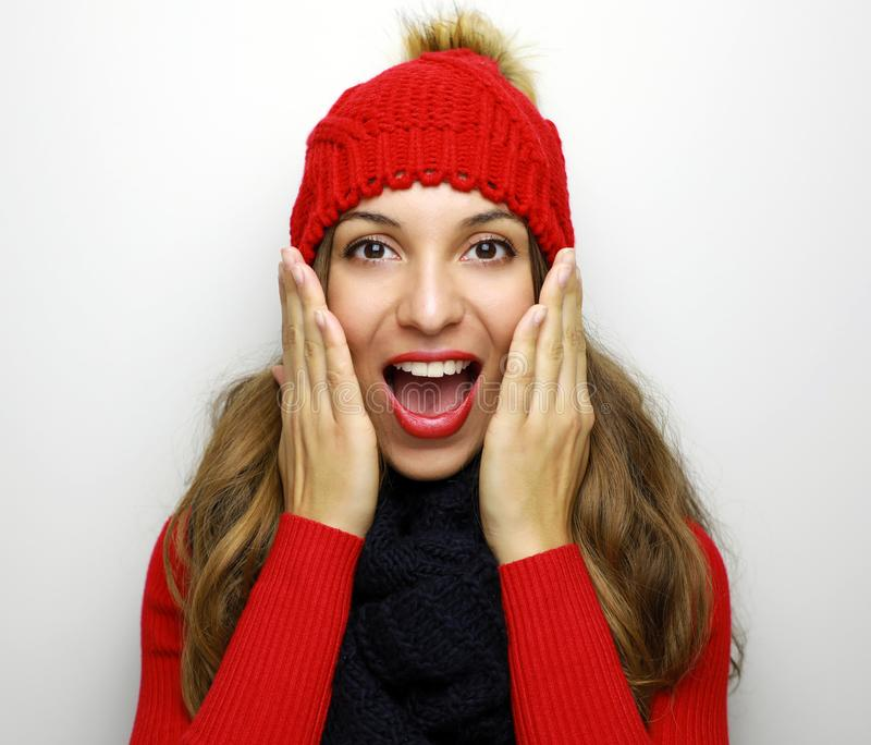 Happy surprised young woman in winter clothes on white background. Sales and discount concept. stock photo