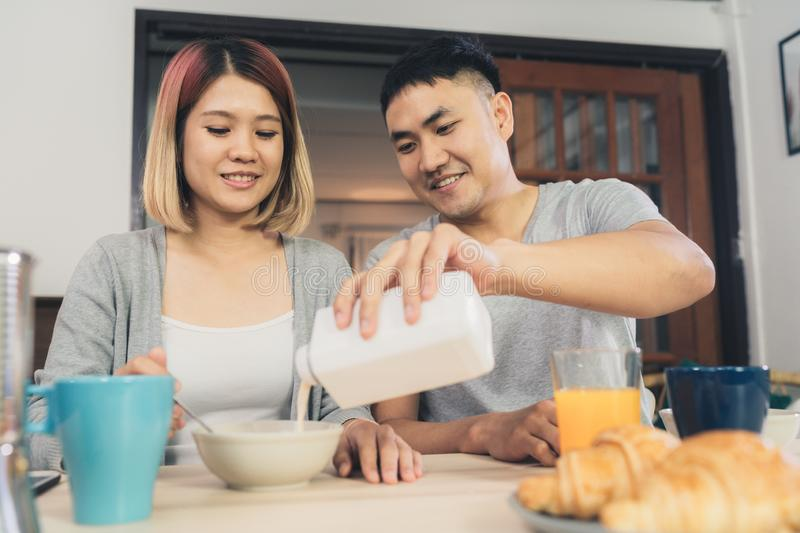 Happy sweet Asian couple having breakfast, cereal in milk, bread and drinking orange juice after wake up in the morning. stock photos