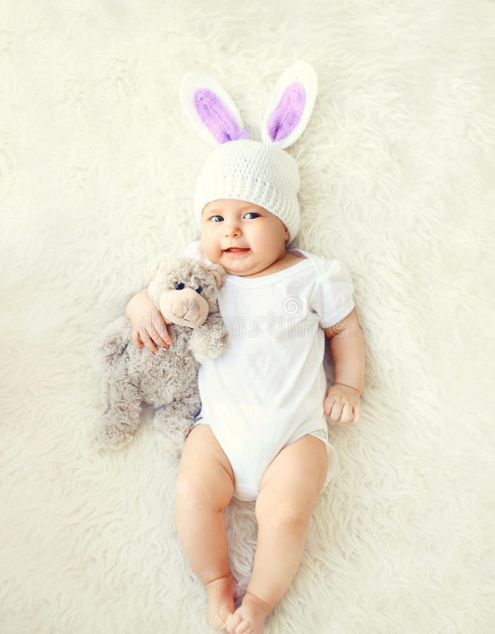 Happy sweet baby in knitted hat with a rabbit ears and teddy bear on bed. Happy sweet baby in knitted hat with a rabbit ears and teddy bear toy lying on bed, top stock photos