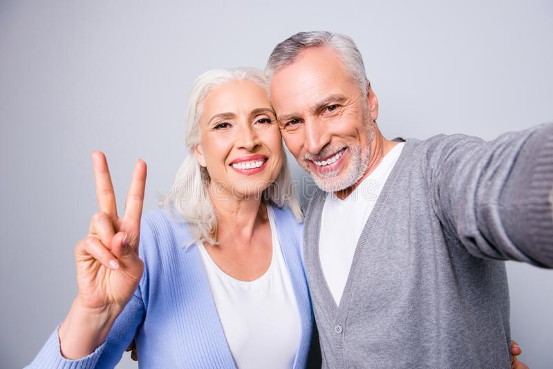 Happy sweet memories! Close up photo of senior couple showing two fingers and taking a selfie, isolated on grey background stock image