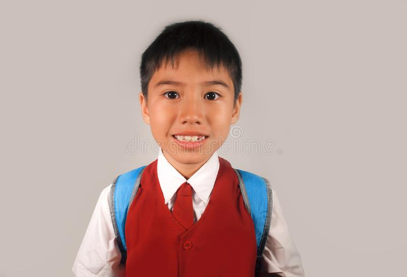 Happy and sweet young schoolboy 7 or 8 years old in school uniform smiling cheerful and excited ready to go back to school carryin royalty free stock photo