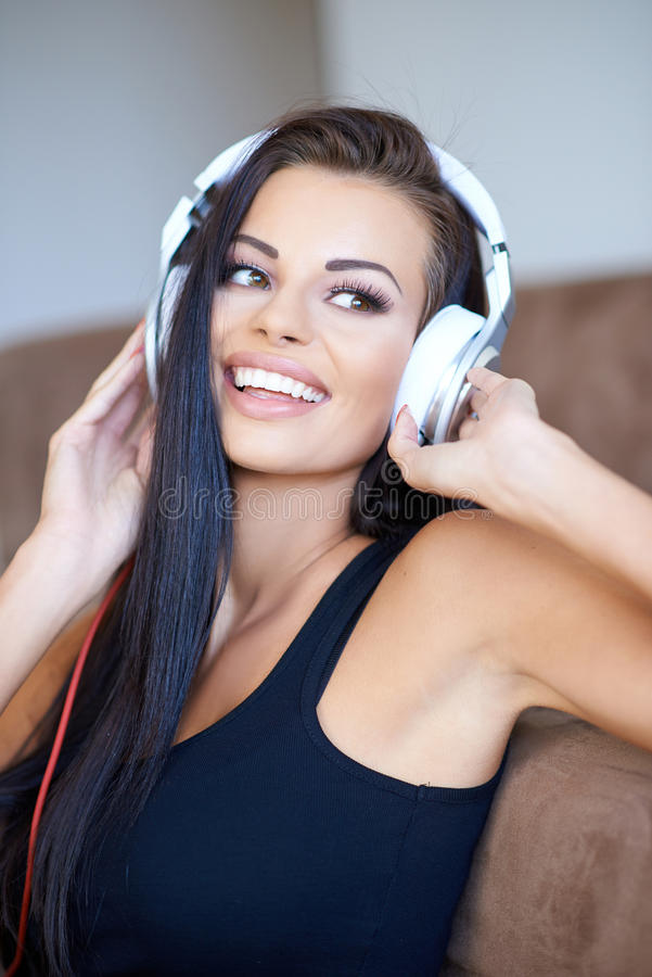 Happy tanned young woman enjoying her music royalty free stock photo