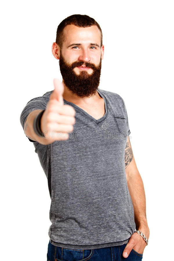 Happy Tattooed bearded man with thumbs up gesture royalty free stock image