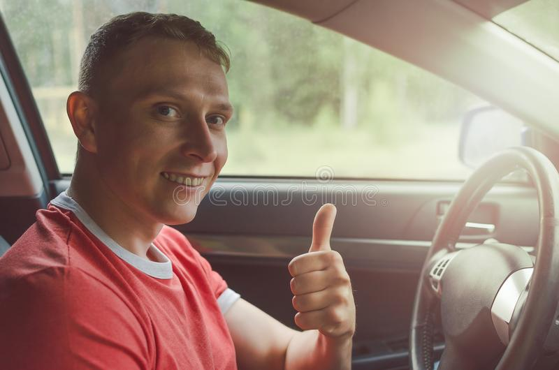 Happy taxi driver. Happy and cheerful taxi driver man is smiling and showing thumbs up. Great car road concept stock image