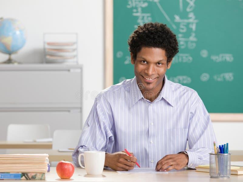 Happy teacher grading papers. In school classroom stock image