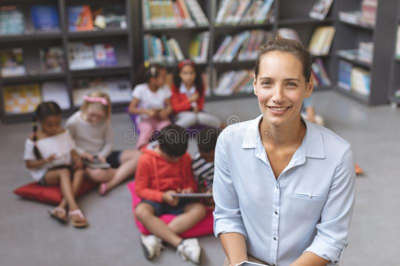 Happy teacher looking and smilling at the camera while school kids relaxing themselves royalty free stock images