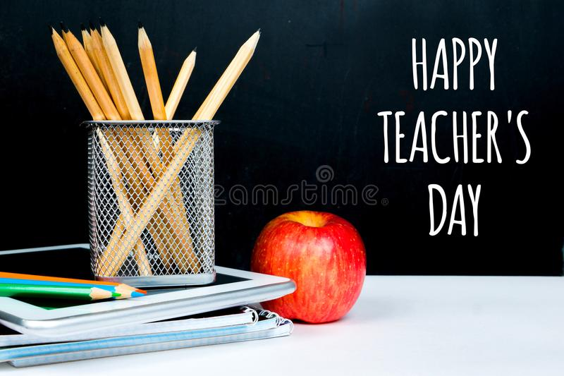 Happy teacher`s day. Chalk greetings on black board in classroom stock photography