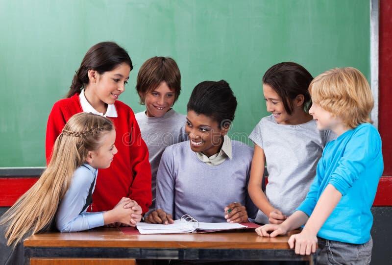 Happy Teacher Teaching Schoolchildren At Desk In stock photography