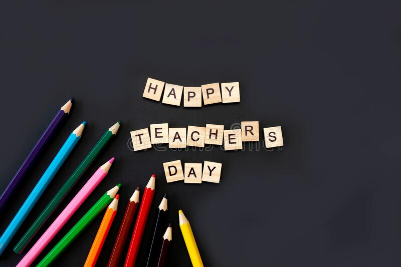 Happy teachers day card. Wooden letters spelling happy teachers day on black background with coloured pencils frame stock photography
